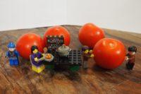 Lego Figuren am Tisch, echte Tomaten im Hintergrund