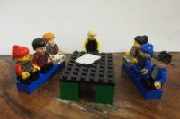 Lego Figuren an einem Tisch sitzend