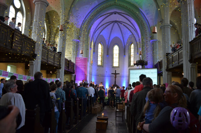 Blick in die volle Friedenskirche, welche mit bläulichem Licht eingeleuchtet ist