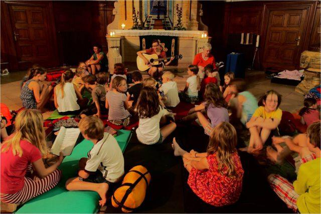 Kinder auf dem Boden vor dem Alter der Michaeliskirche Leipzig singen